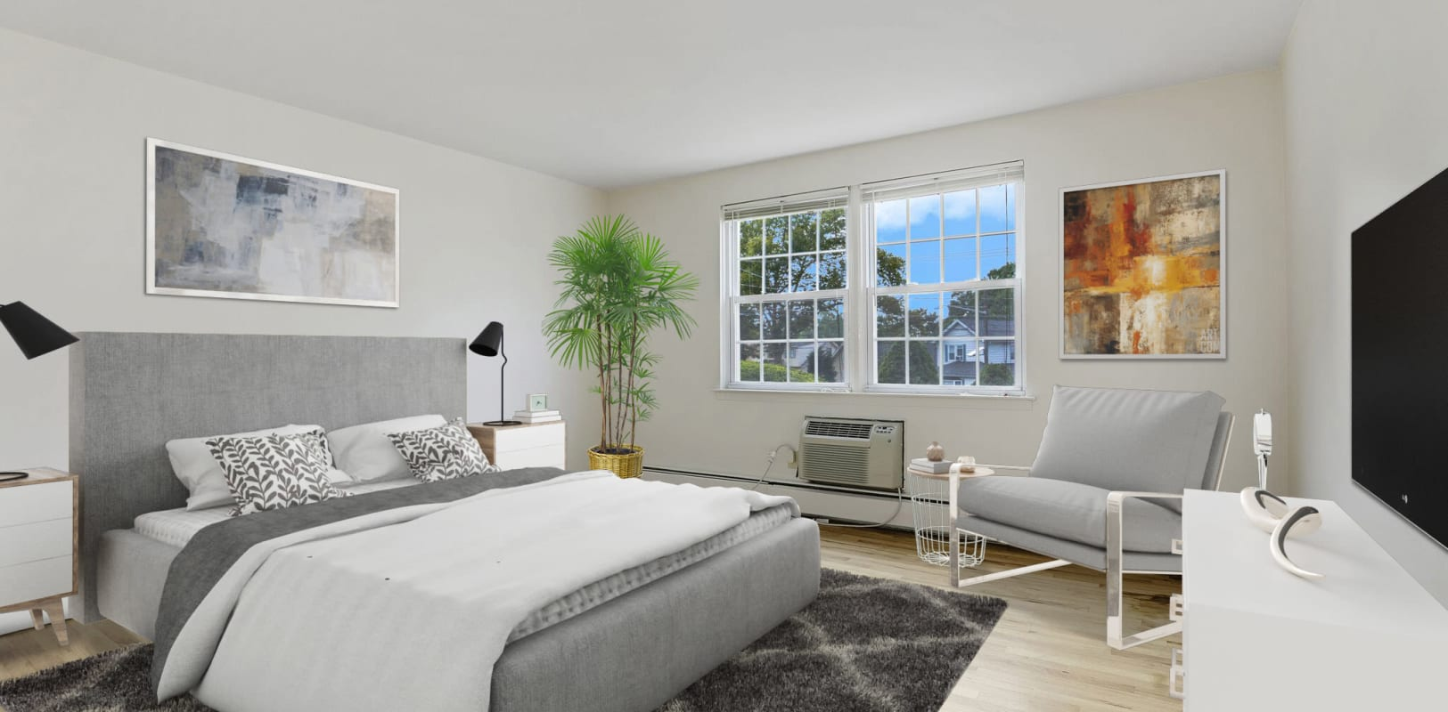Staged lovely bedroom with floor rug and ample space at Parkway East Apartments in Caldwell, New Jersey
