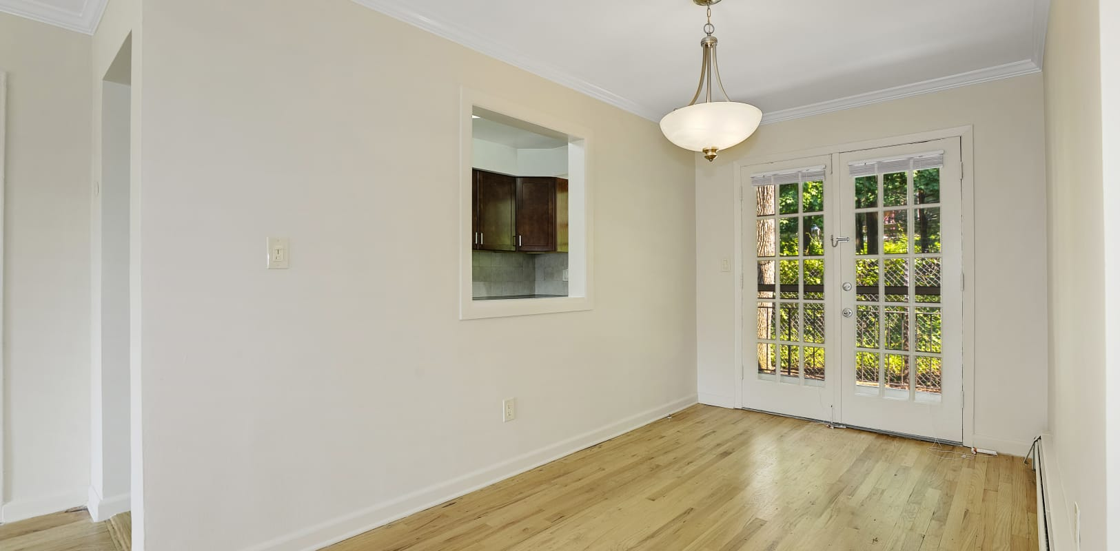 Lovely dining room with wood style flooring and hanging light at Parkway East Apartments in Caldwell, New Jersey