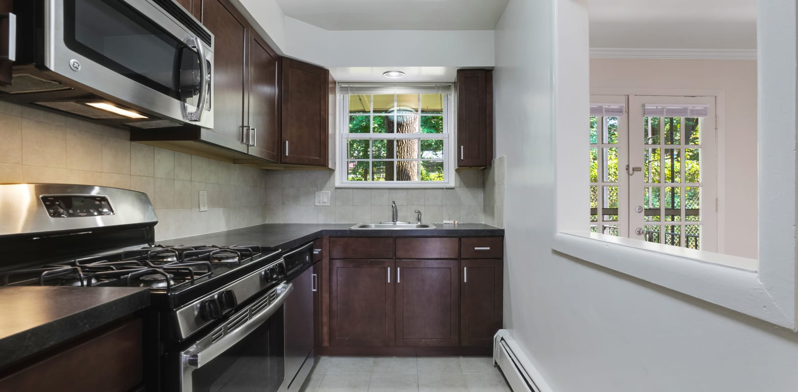 Kitchen with dark wood cabinets and nice black and silver appliances at Parkway East Apartments in Caldwell, New Jersey