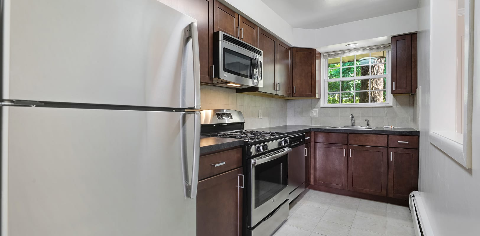 Clean kitchen with stainless steel appliances at Parkway East Apartments in Caldwell, New Jersey
