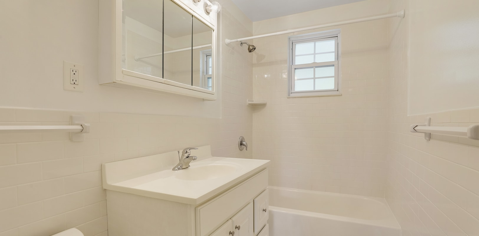 Bathroom with white cabinets and window next to shower for outdoor views at Parkway East Apartments in Caldwell, New Jersey
