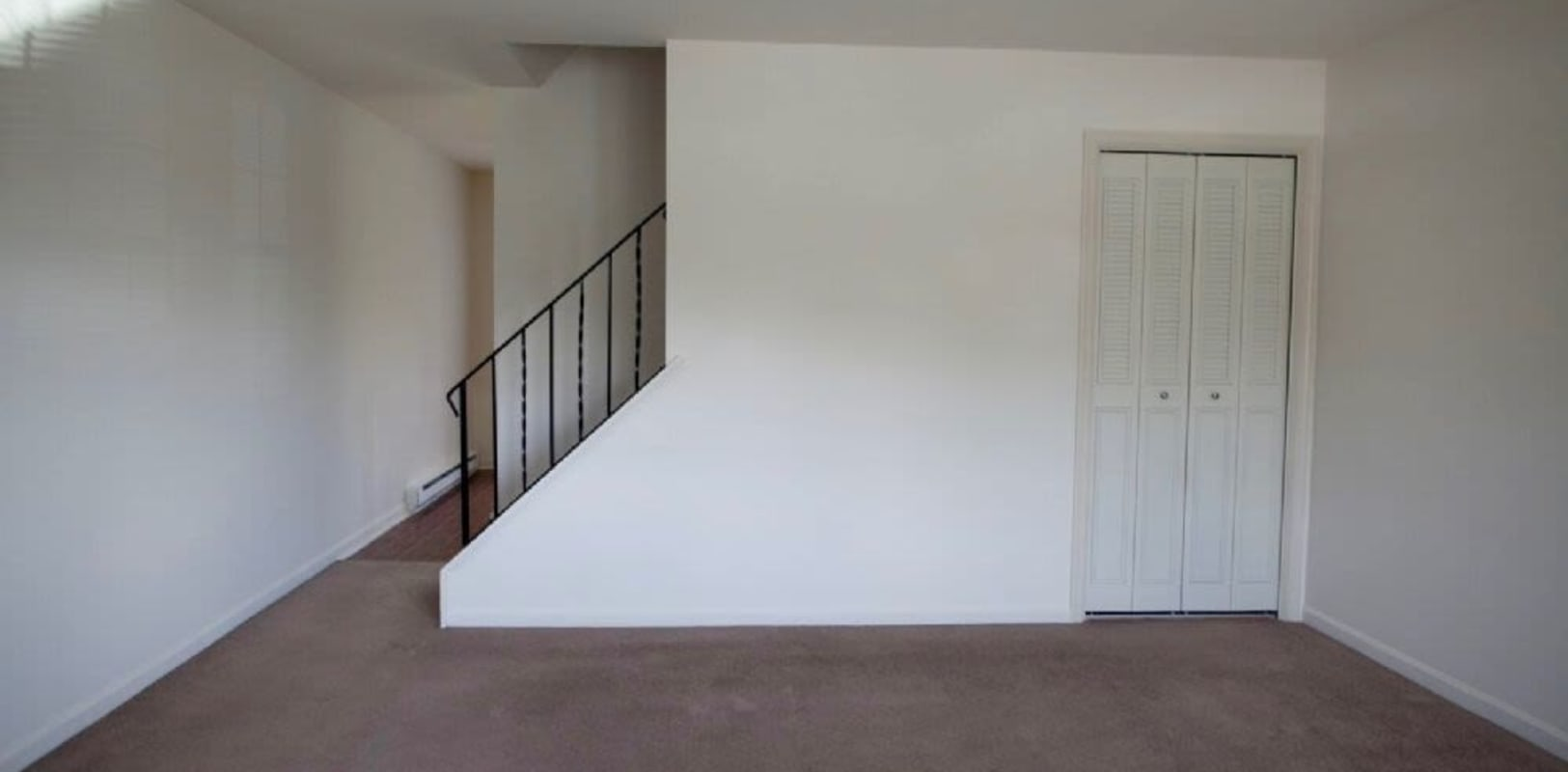 Empty carpeted living room with stairs to upper level at Oley Meadows in Oley, Pennsylvania