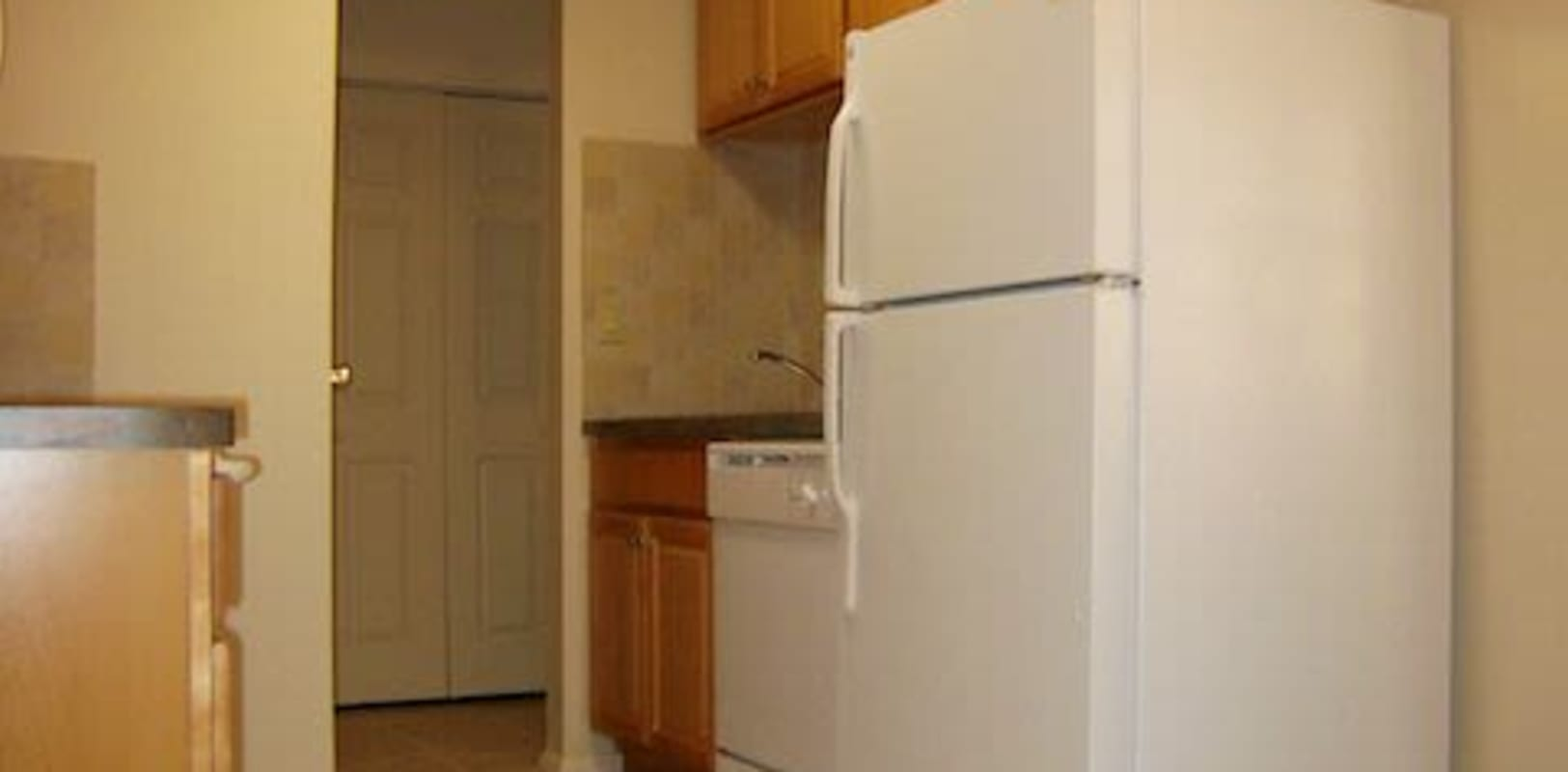 Kitchen with wooden cabinets and a white fridge at Pine Crest Apartments in Milford, New Jersey