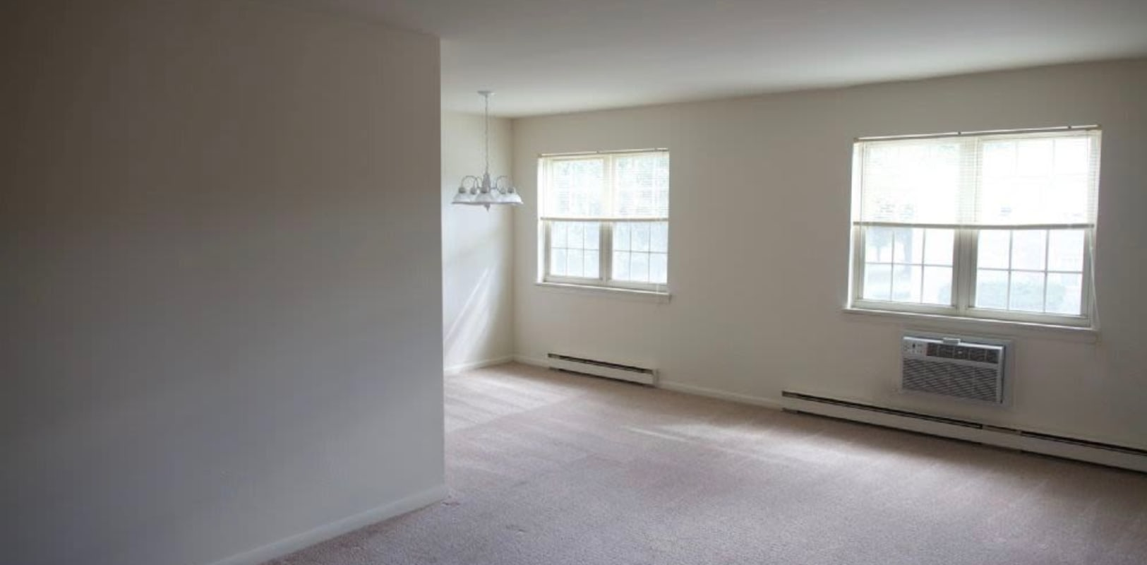 Large carpeted living room with lots of natural light at Sharon Arms Apartments in Robbinsville, New Jersey