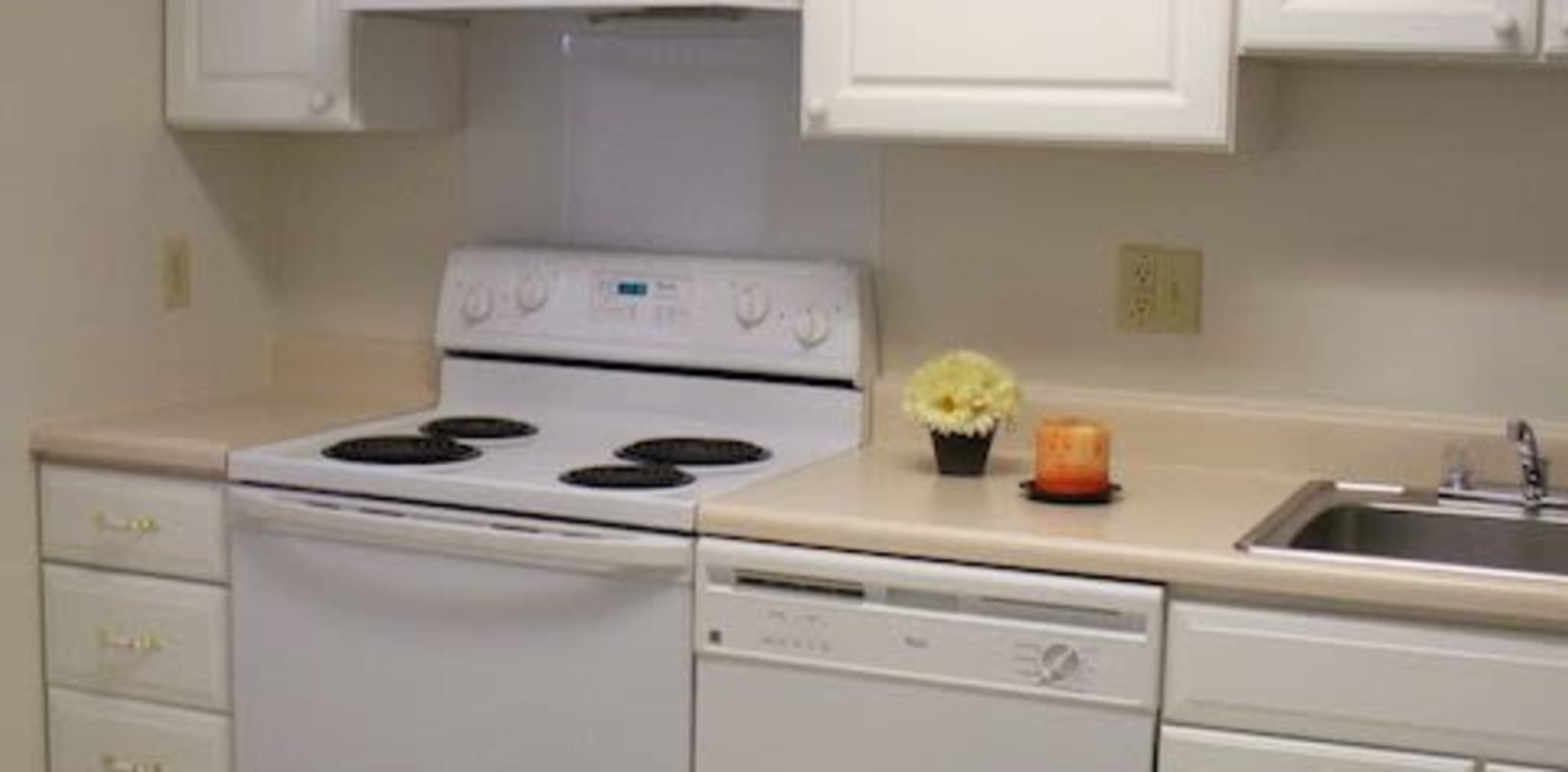 Kitchen with beige countertops and white cabinets at Spring Valley Apartments in Sinking Spring, Pennsylvania