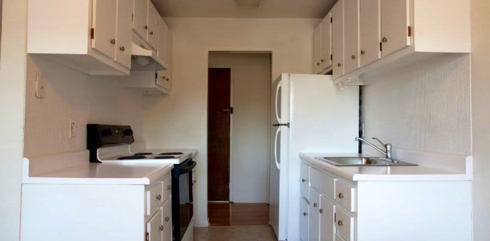 Kitchen with all white cabinets at Versailles Apartments in Ewing, New Jersey