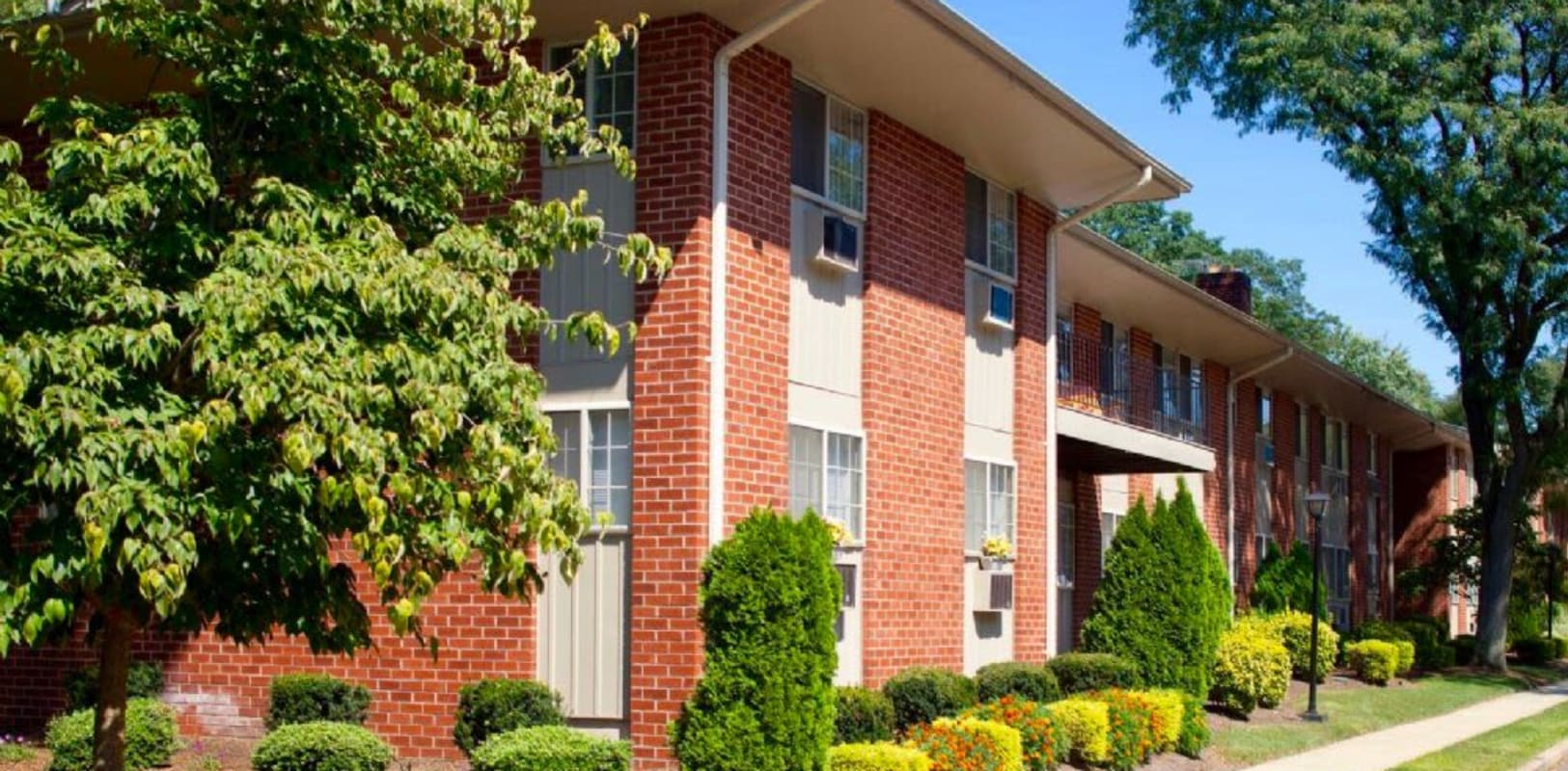 Exterior walkway with lots of plants and a nice lawn at Versailles Apartments in Ewing, New Jersey