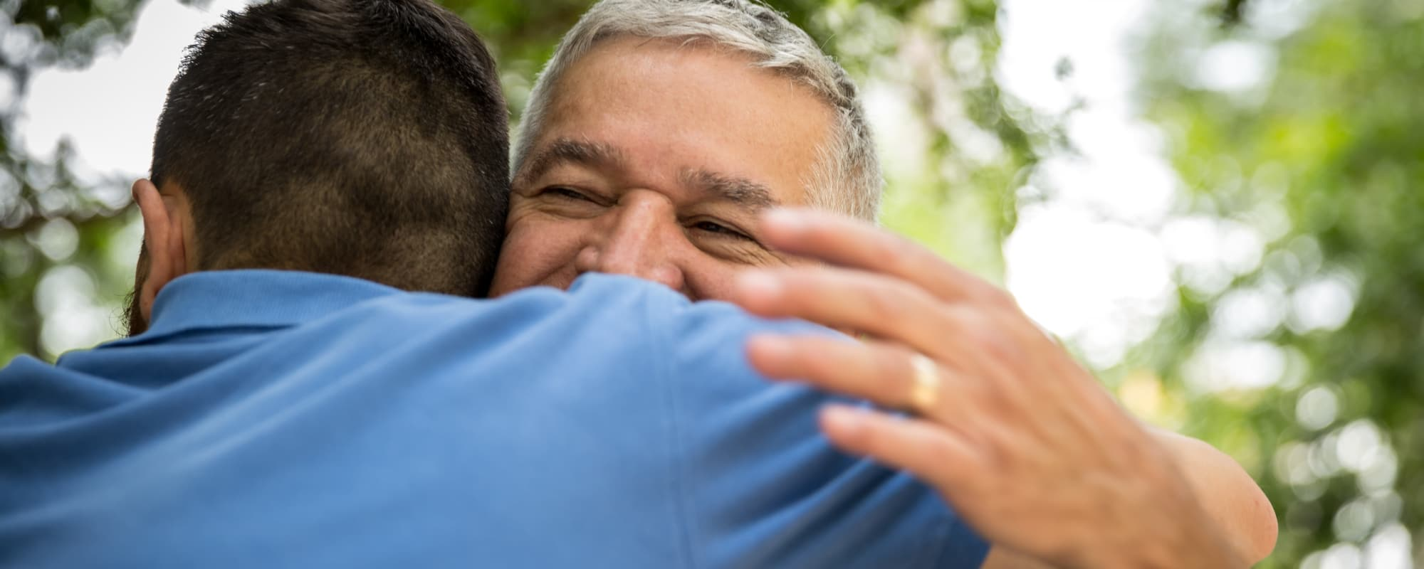 A resident hugging his son at Almond Heights in Orangevale, California
