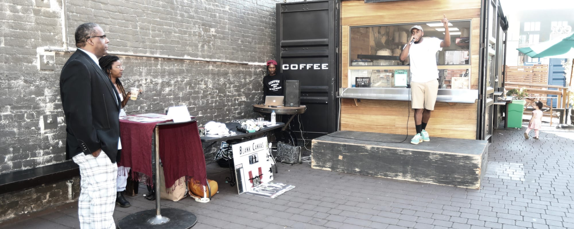 Coffee cart with an outdoor performer near The Moran in Oakland, California