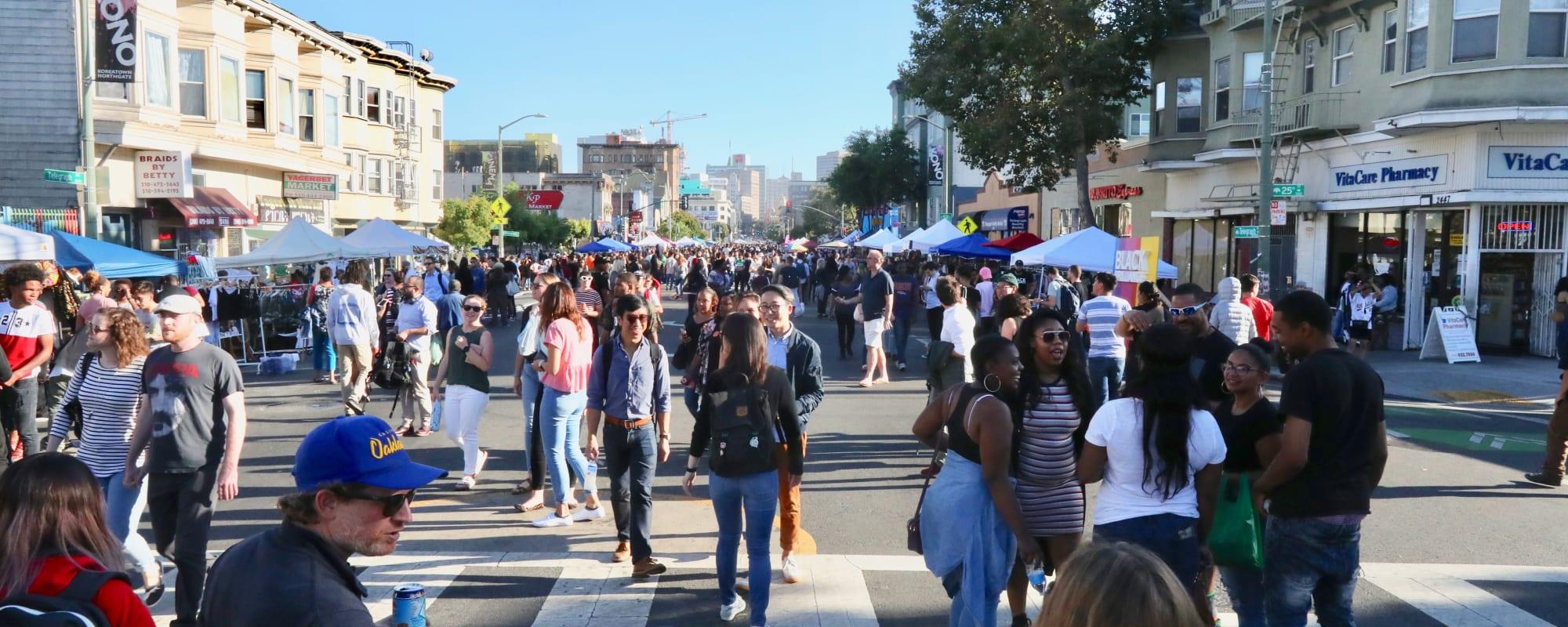 Bright street with walking people near The Moran in Oakland, California