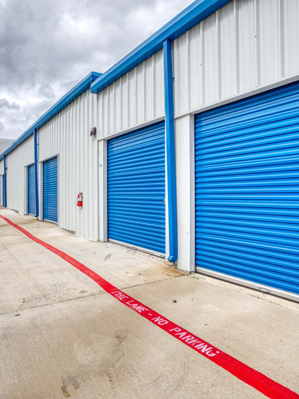 Blue roll-up doors to storage units at Devon Self Storage in Fort Worth, Texas