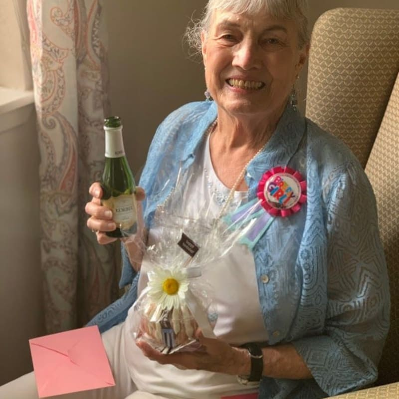 Resident receiving a gift at Golden Pond Retirement Community in Sacramento, California