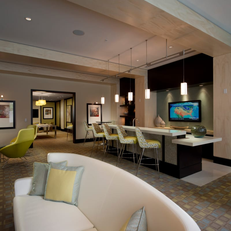A modern clubhouse with bar seating and a flat-screen TV at Solaire 1150 Ripley in Silver Spring, Maryland