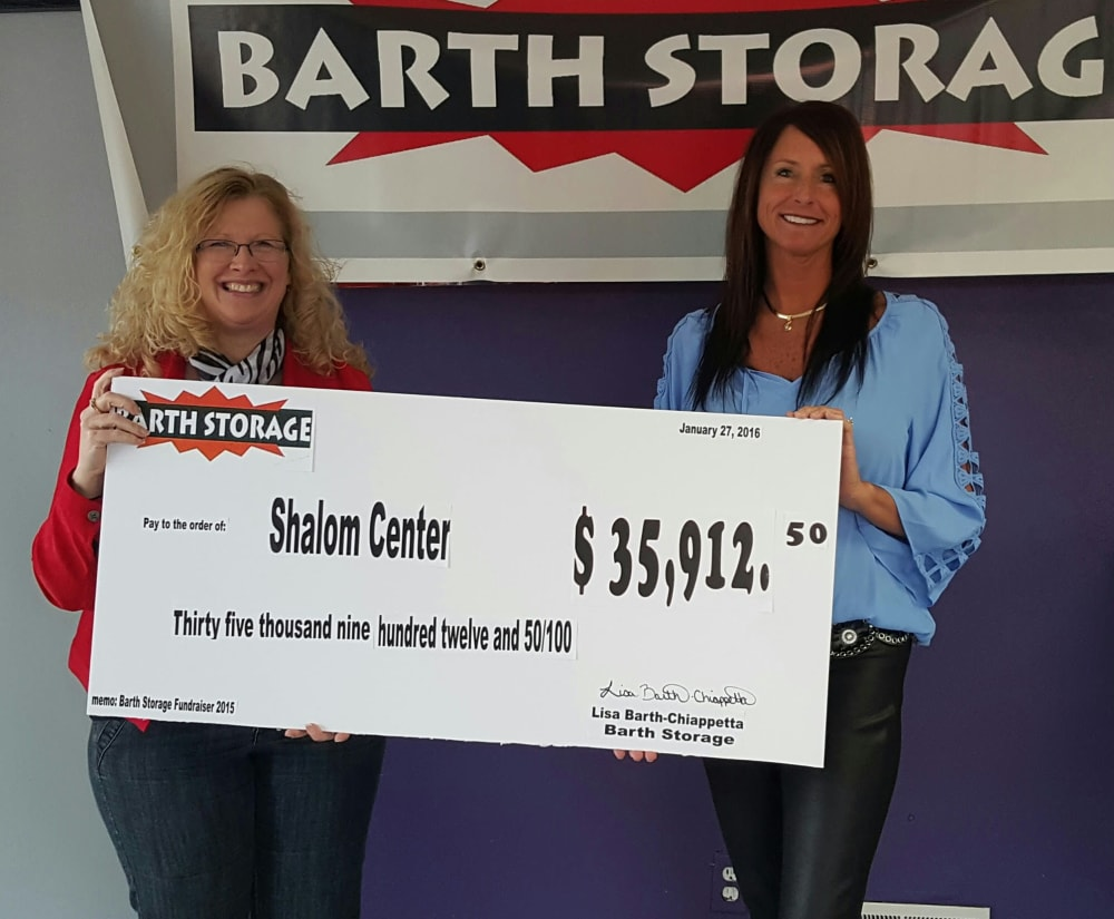 Barth Storage employees holding up how much money was donated to a local charity in Kenosha, Wisconsin