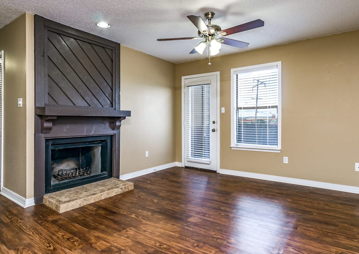 Model apartment home at North Pointe Apartments with a fireplace, hardwood floors, and ceiling fan