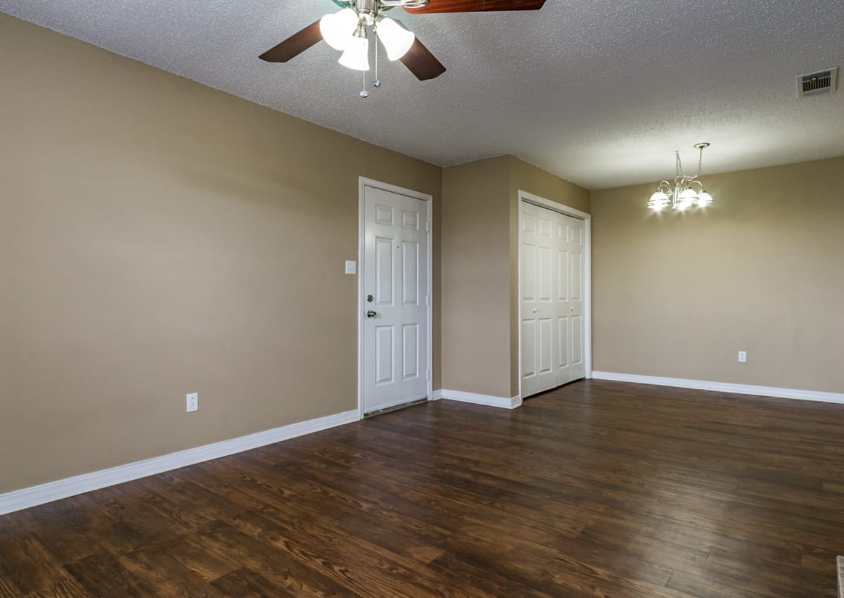 Open-concept living area with custom lighting, hardwood floors, and ceiling fan at North Pointe Apartments