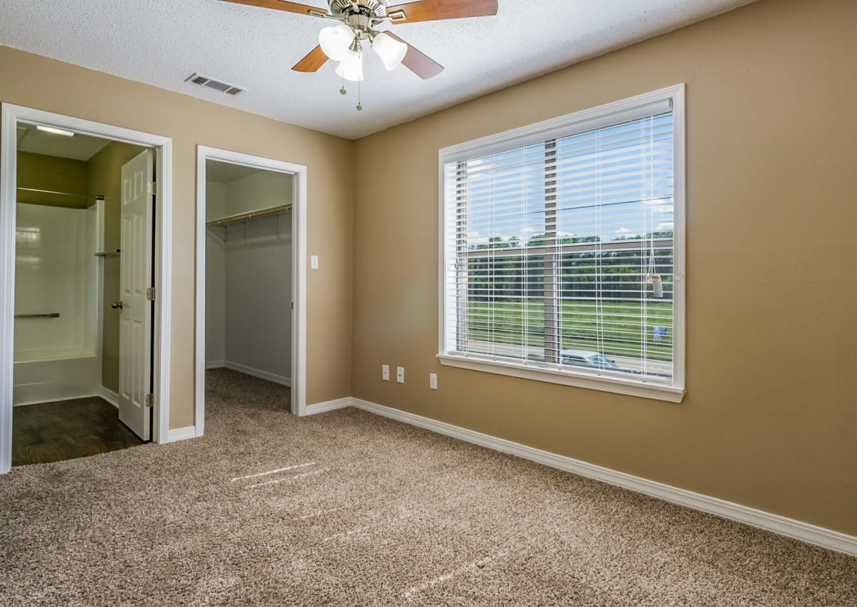 Bedroom in model home at North Pointe Apartments with plenty of natural light, ceiling fan, and ensuite bathroom