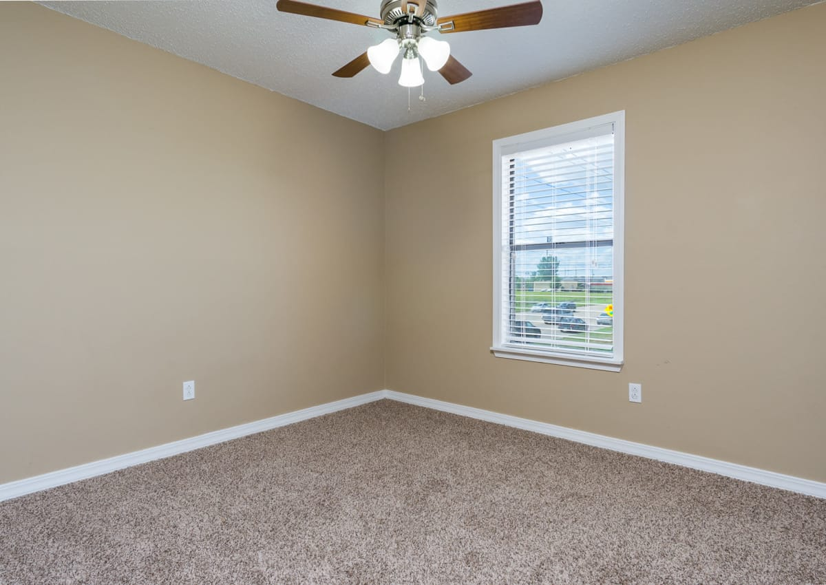 View of bedroom at North Pointe Apartments with plush carpeting and ceiling fan