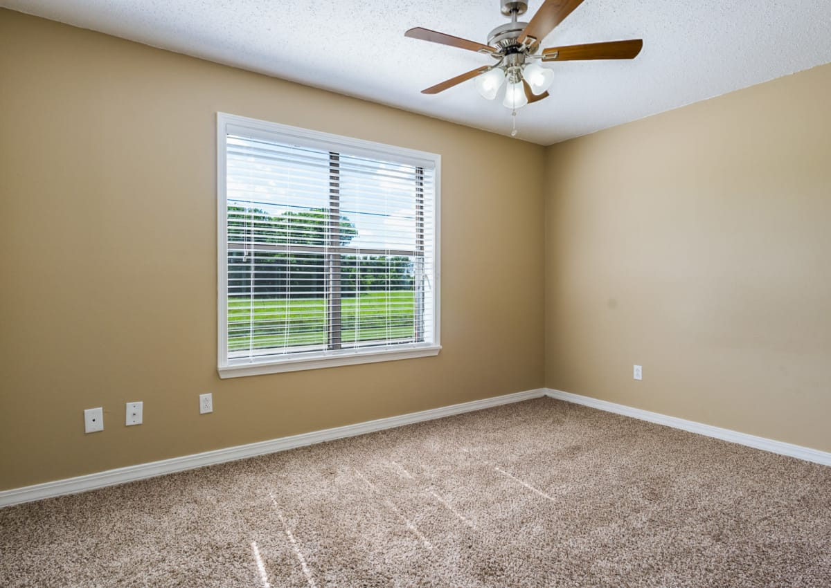Guest bedroom or office in model home at North Pointe Apartments with ceiling fan and natural light
