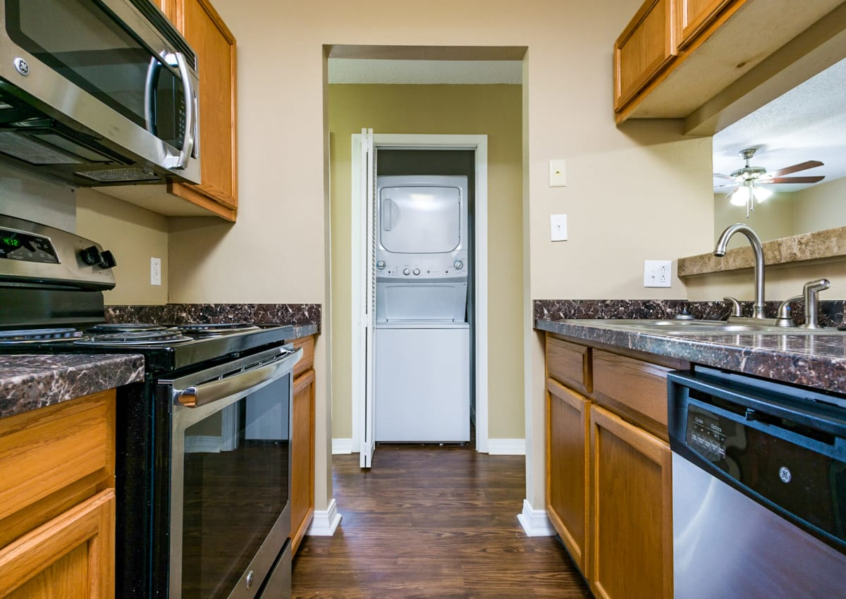 Modern and well-equipped kitchen with stainless-steel appliances and washer/dryer in the background at North Pointe Apartments