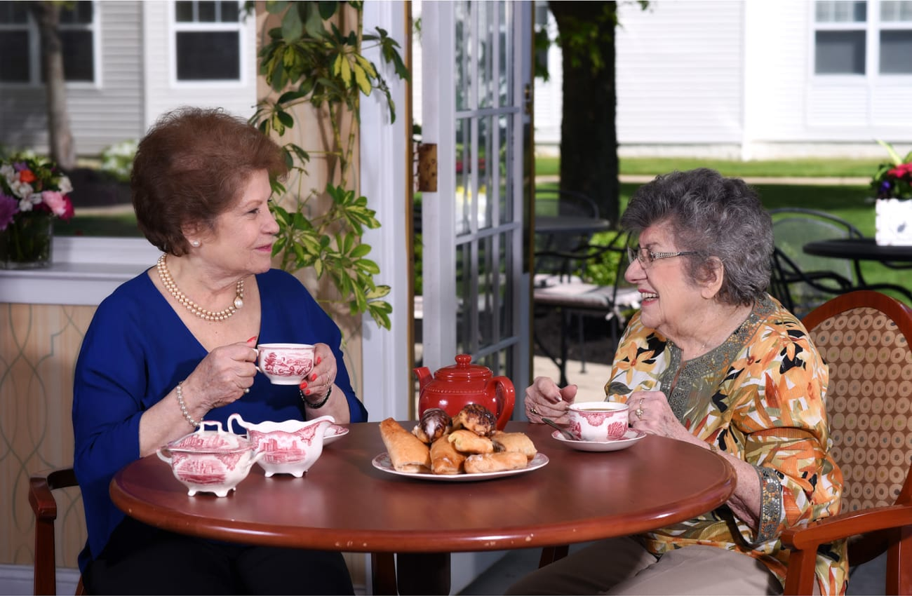 Two senior women laughing over tea