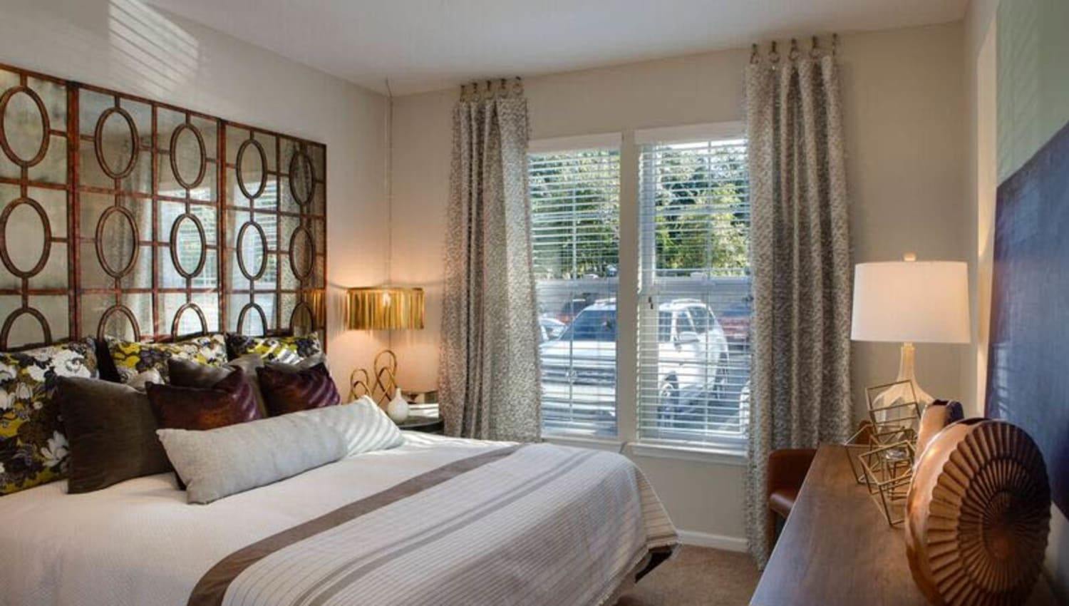 Large bay window and modern furnishings in a model home's master bedroom at Canopy at Citrus Park in Tampa, Florida