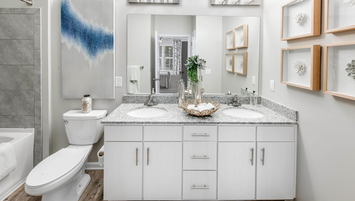 Large vanity mirror and a granite countertop in a model home's bathroom at Canopy at Citrus Park in Tampa, Florida