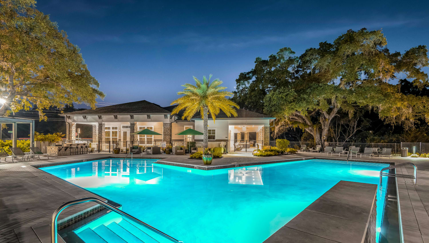 Even view of the pool with underwater lights on at Canopy at Citrus Park in Tampa, Florida