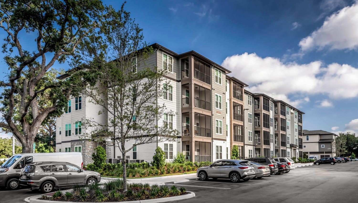 Mature trees and ample parking outside resident buildings at Canopy at Citrus Park in Tampa, Florida