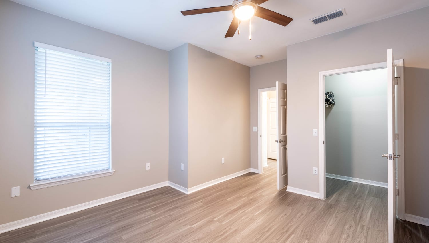 Bedroom with hardwood flooring and a ceiling fan in a model home at Cape House in Jacksonville, Florida