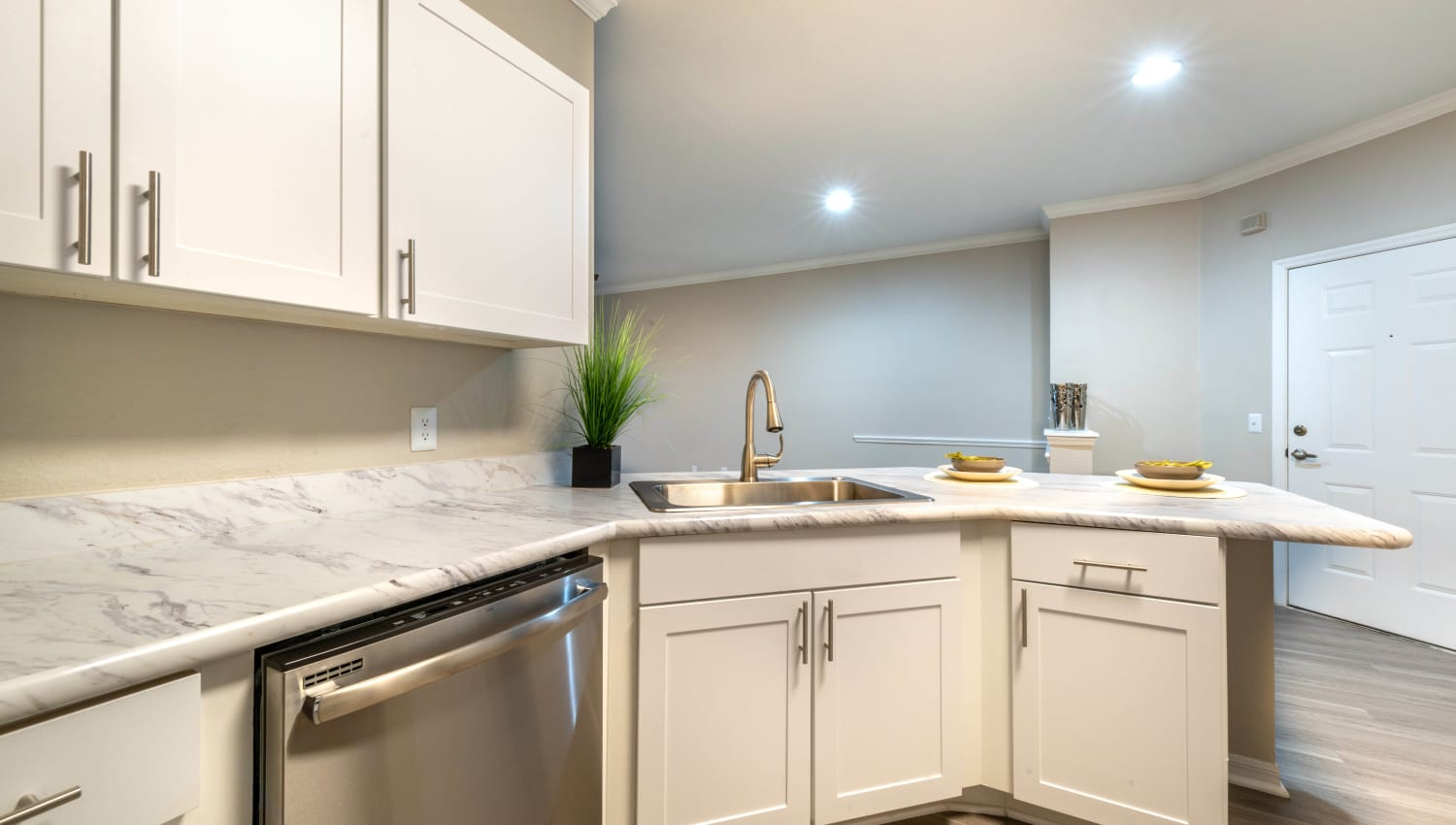 Bright white cabinetry in the kitchen of a model home at Cape House in Jacksonville, Florida
