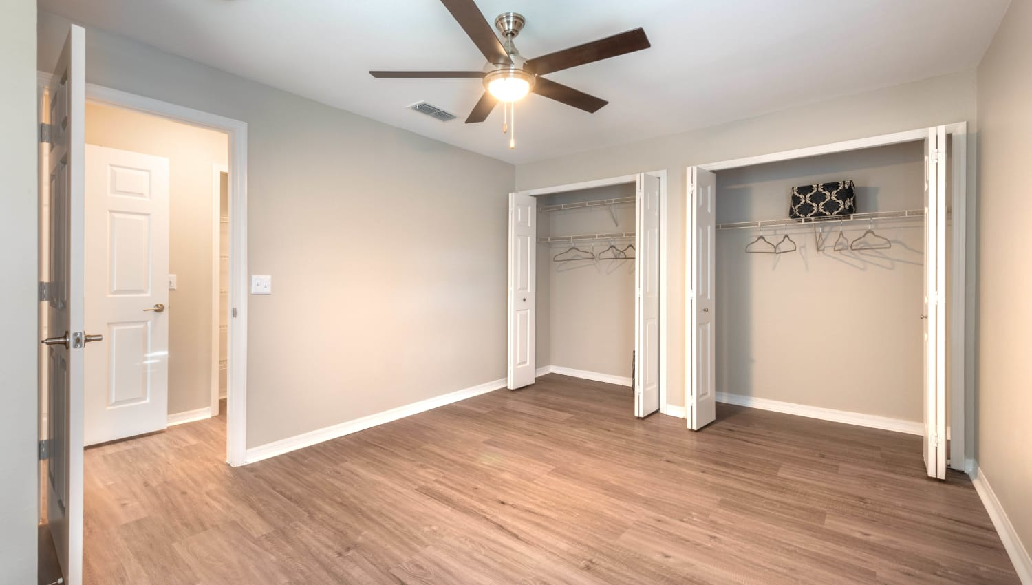 Master bedroom with ample closet space and a ceiling fan in a model home at Cape House in Jacksonville, Florida