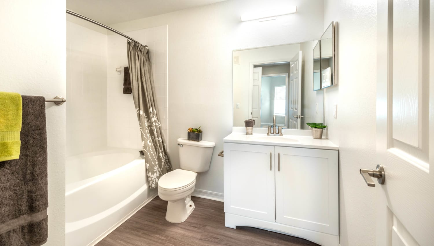 Bright bathroom with a large vanity mirror in a model home at Cape House in Jacksonville, Florida