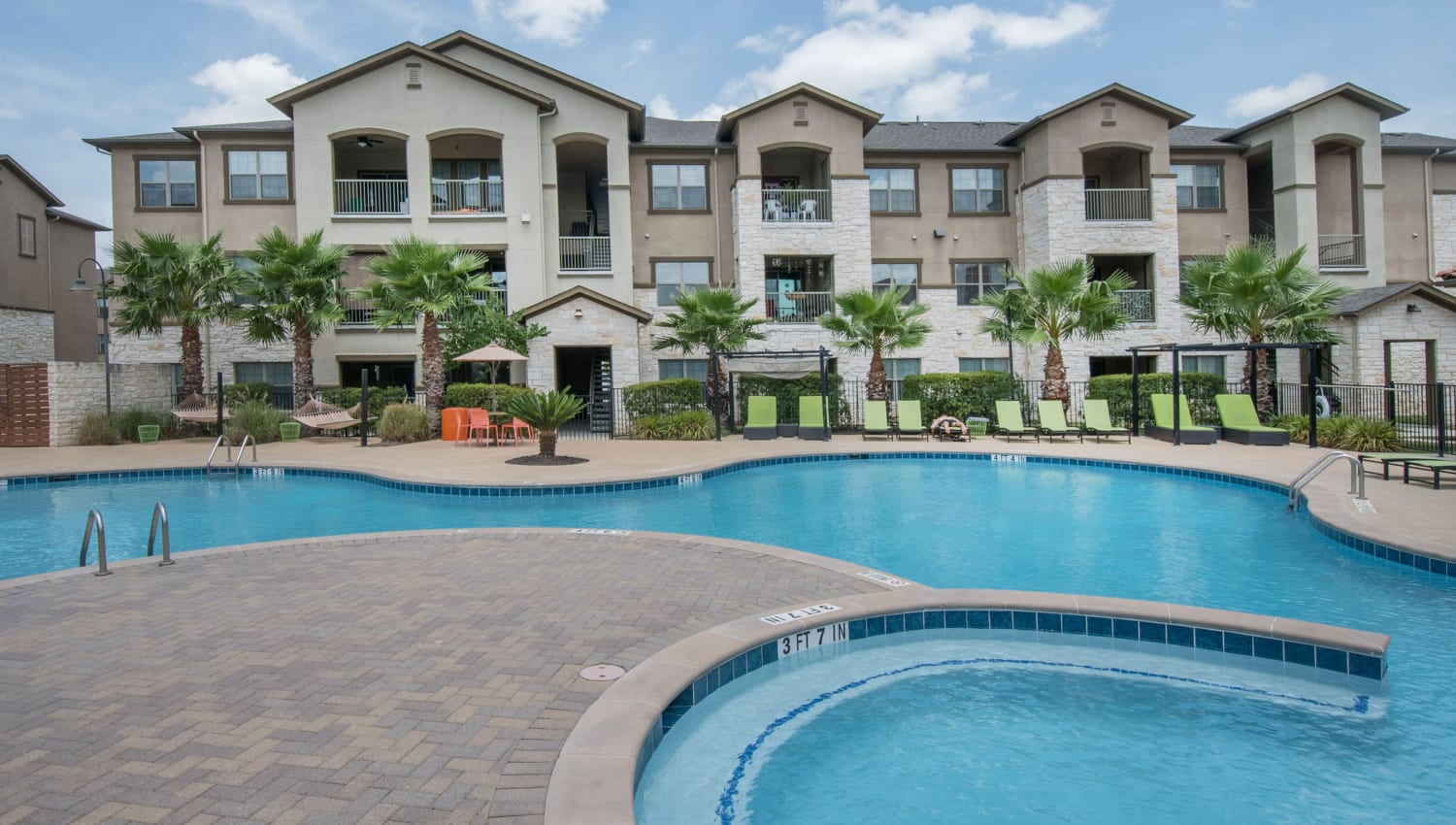 Resort-style swimming pool surrounded by palm trees at Carrington Oaks in Buda, Texas