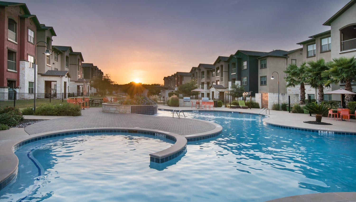 View of the sun rising above the swimming pool at Carrington Oaks in Buda, Texas
