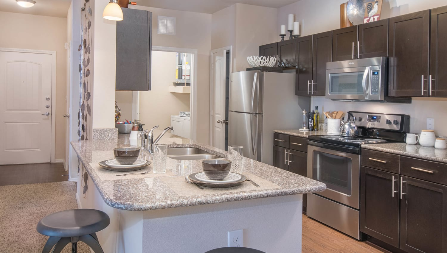 Gourmet kitchen in the open-concept floor plan of a model apartment home at Carrington Oaks in Buda, Texas