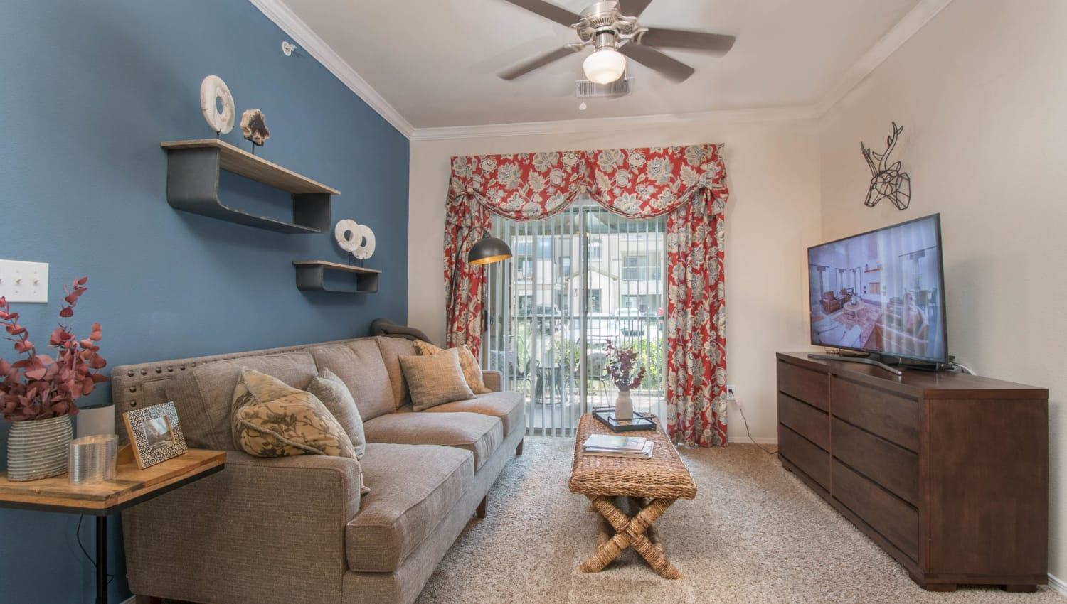 Accent wall and a ceiling fan in the comfortably furnished living area of a model apartment at Carrington Oaks in Buda, Texas