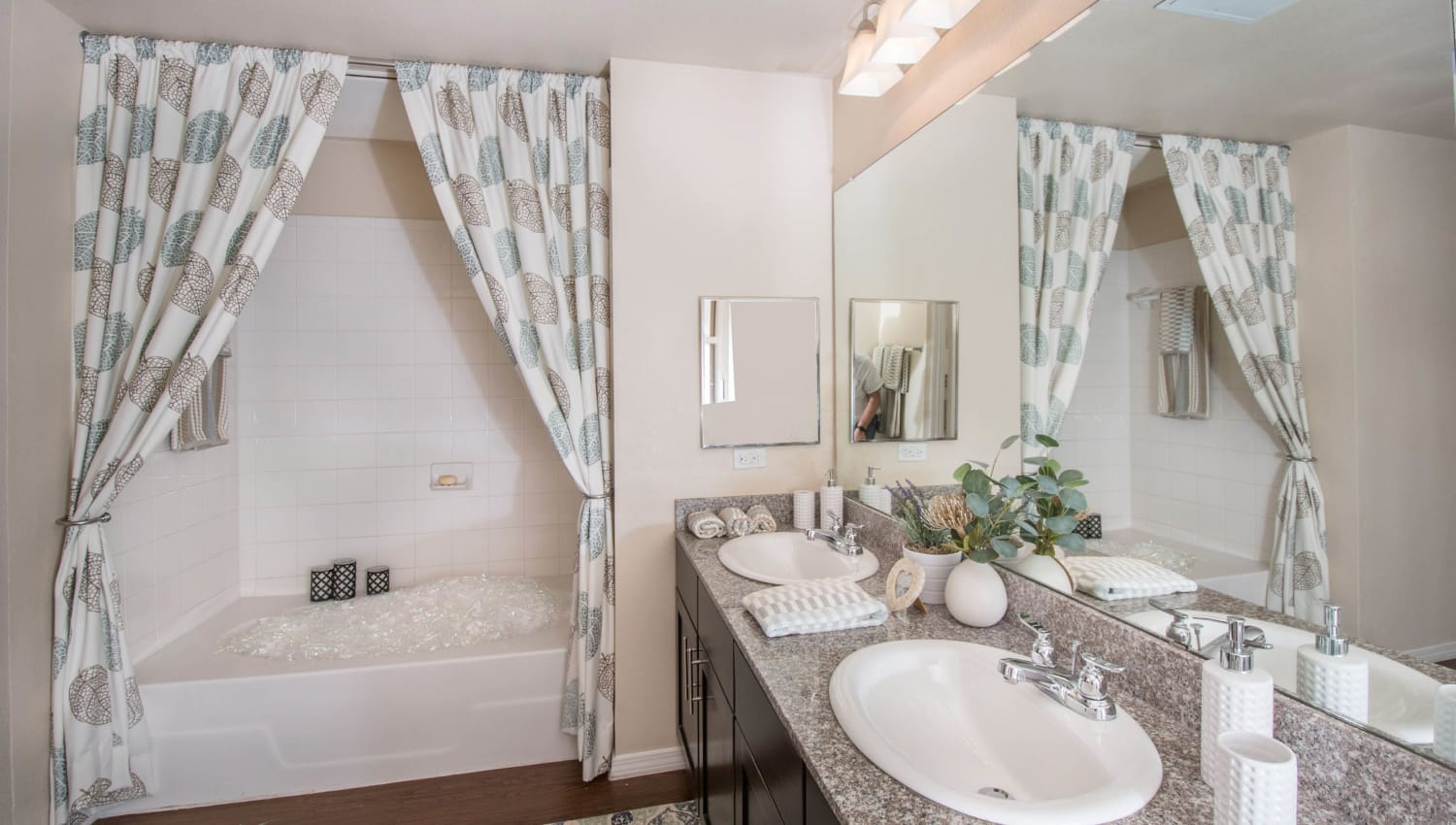Master bathroom with an oval tub and two sinks in a model apartment at Carrington Oaks in Buda, Texas