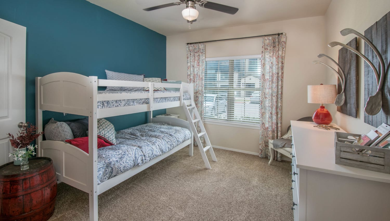 Child's bedroom with an accent wall and a ceiling fan in a model home at Carrington Oaks in Buda, Texas