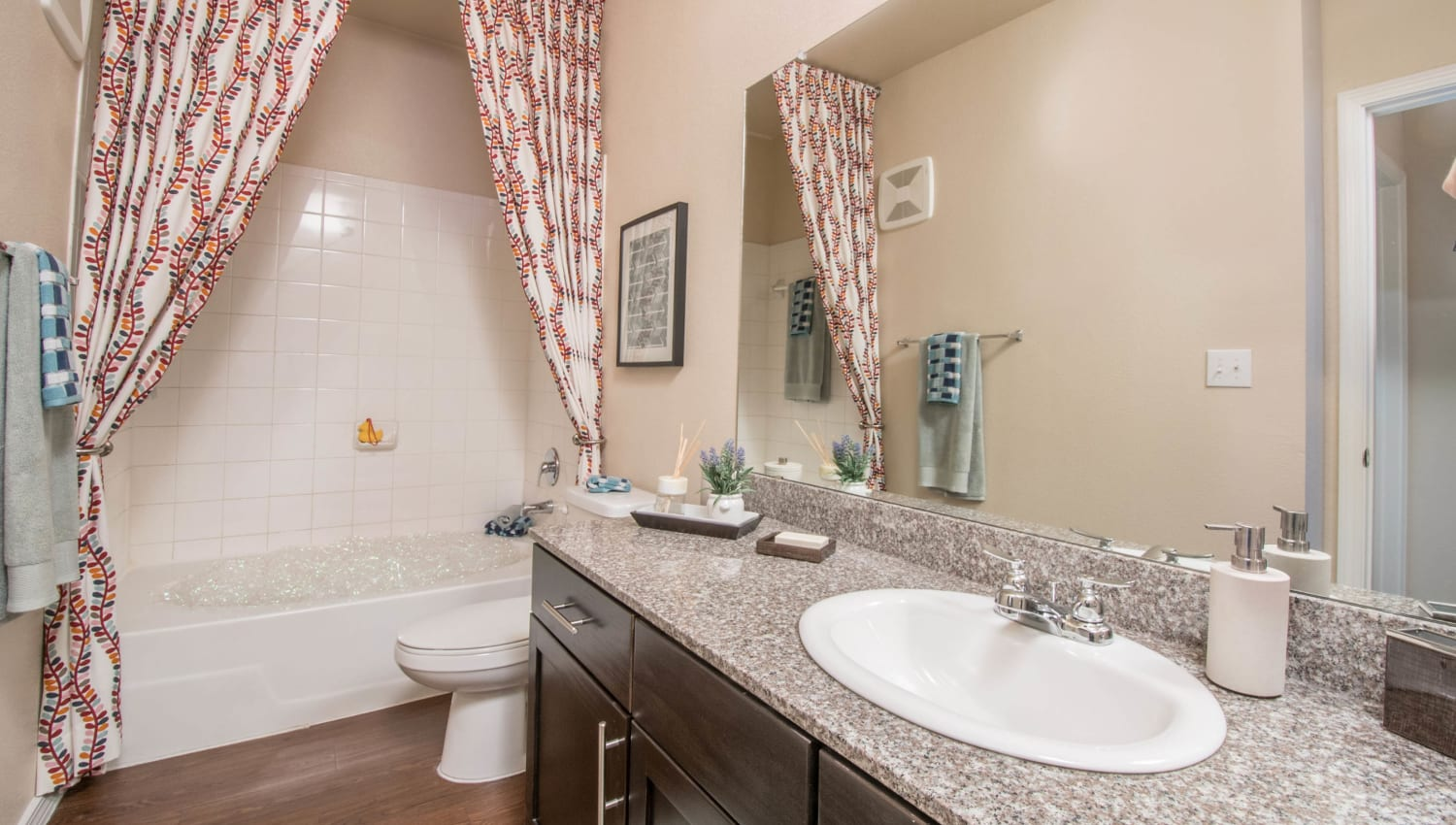 Guest bathroom with a granite countertop in a model apartment at Carrington Oaks in Buda, Texas