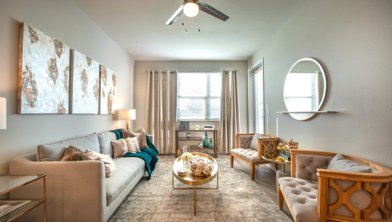 Ceiling fan and comfortable furnishings in the living space of a model home at Olympus at Daybreak in South Jordan, Utah