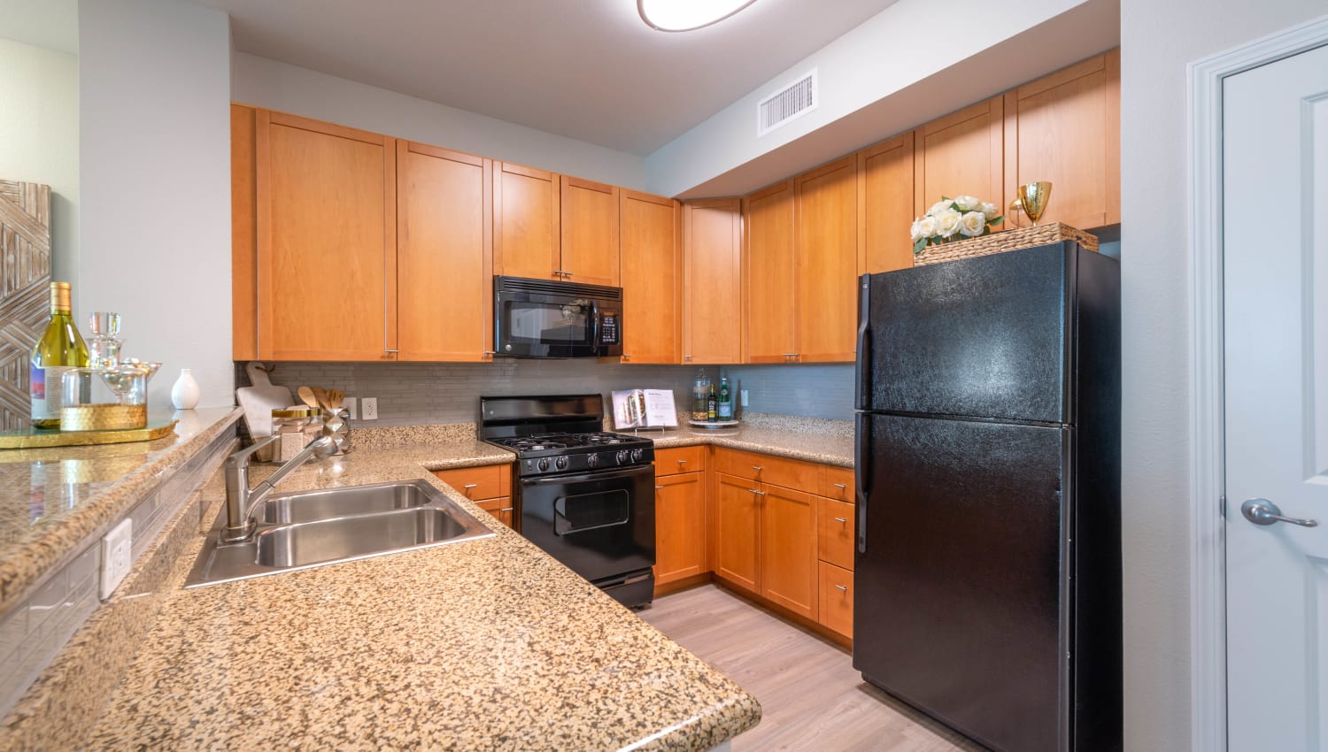 Black appliances and custom wood cabinetry in a model home's kitchen at Olympus at Daybreak in South Jordan, Utah