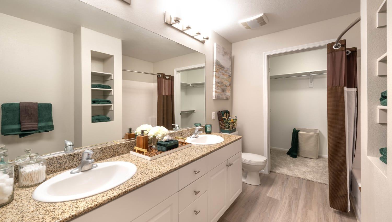 Large vanity mirror and hardwood flooring in a model home's master bathroom at Olympus at Daybreak in South Jordan, Utah