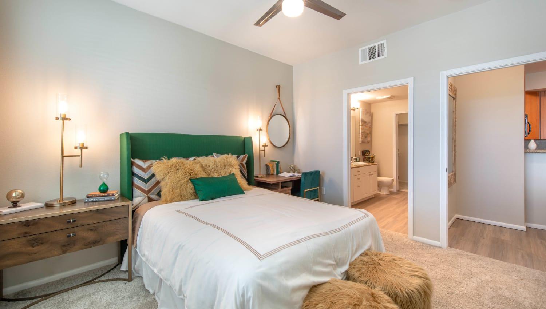 Ceiling fan and an en suite bathroom in a model apartment's master bedroom at Olympus at Daybreak in South Jordan, Utah