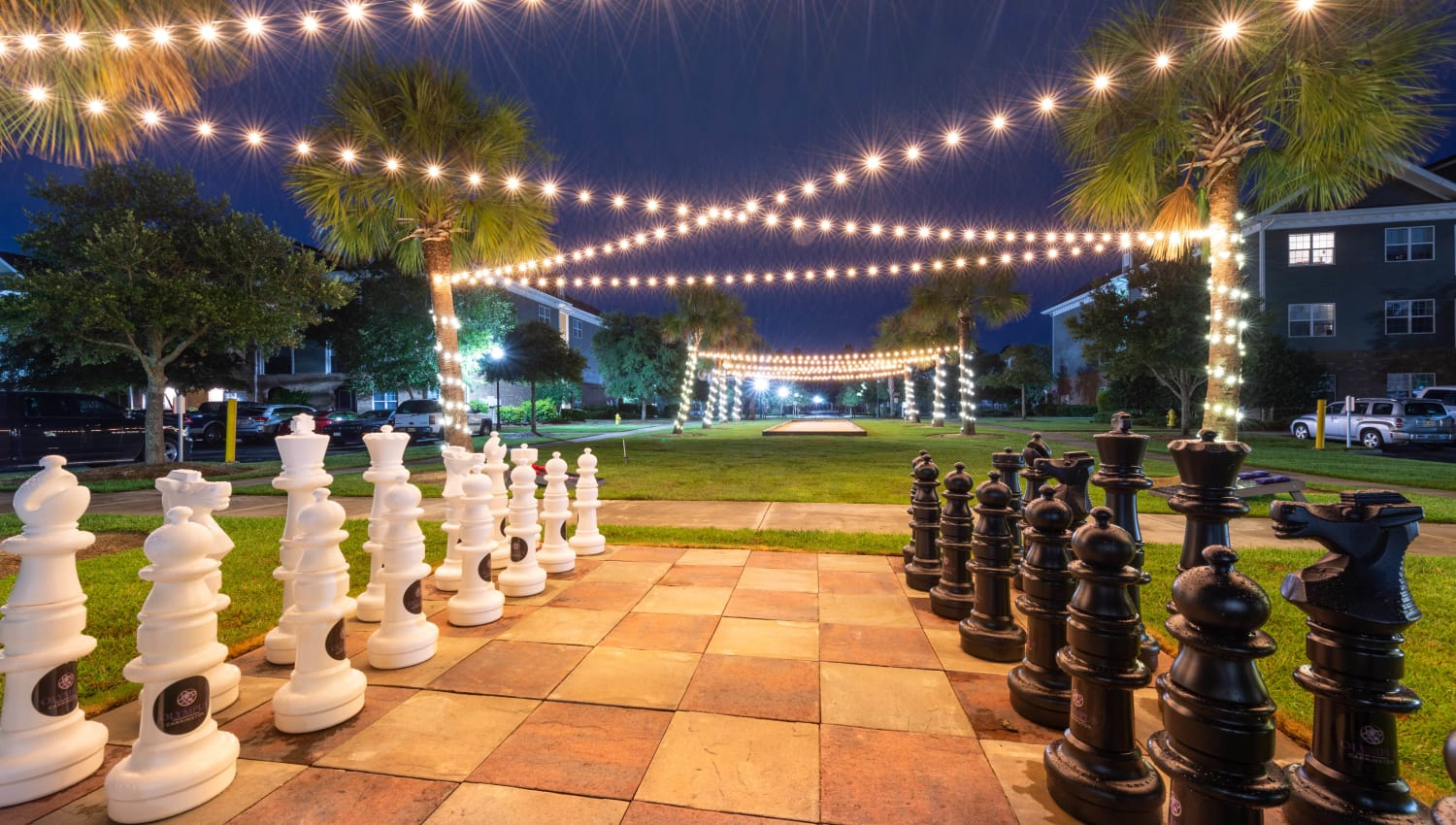 String lights above the life-size chessboard in the evening at Olympus Carrington in Pooler, Georgia