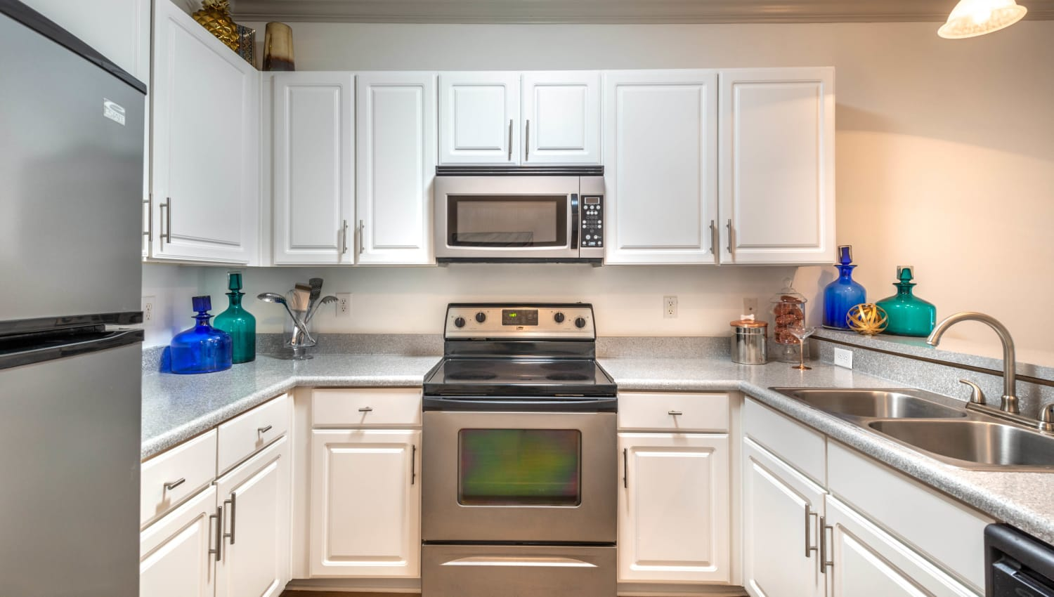 Model apartment's spacious kitchen with ample cupboard space for storage at Olympus Carrington in Pooler, Georgia