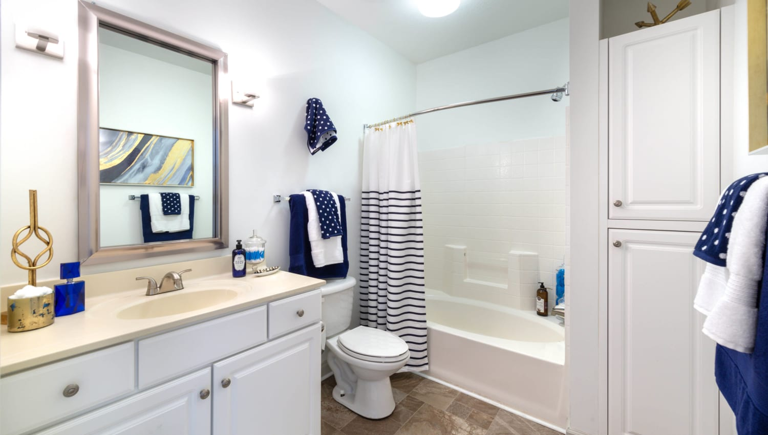 Model home's master bathroom with a tiled shower and extra cupboard storage at Olympus Carrington in Pooler, Georgia