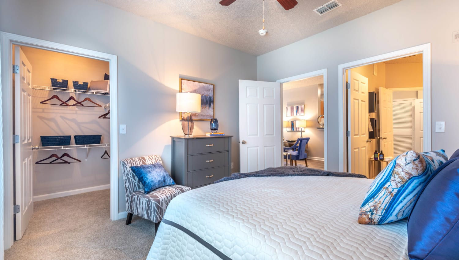 Model home's guest bedroom with a walk-in closet at Olympus Fenwick in Savannah, Georgia