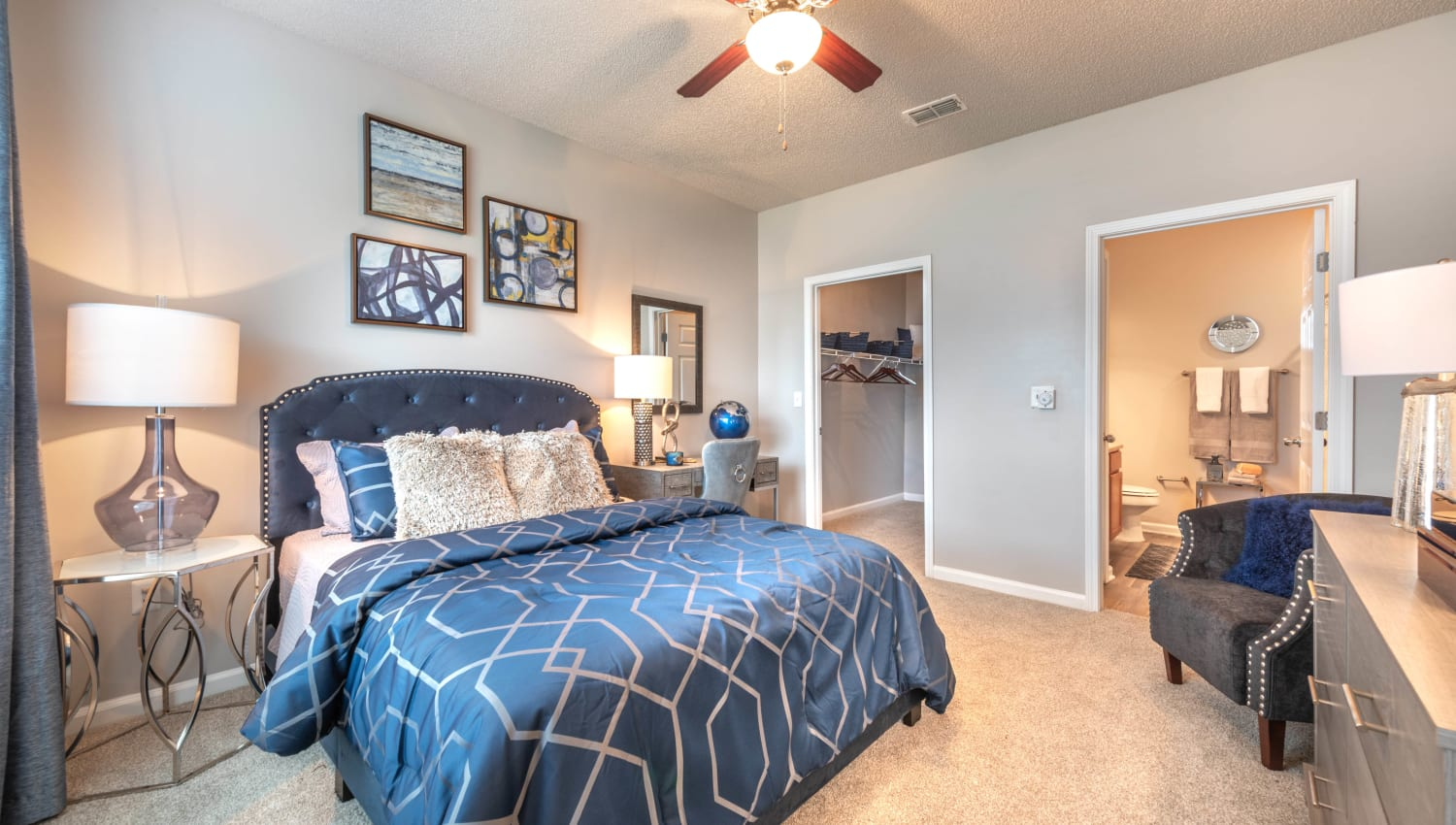 Ceiling fan and plush carpeting in the well-furnished master bedroom of an apartment home at Olympus Fenwick in Savannah, Georgia