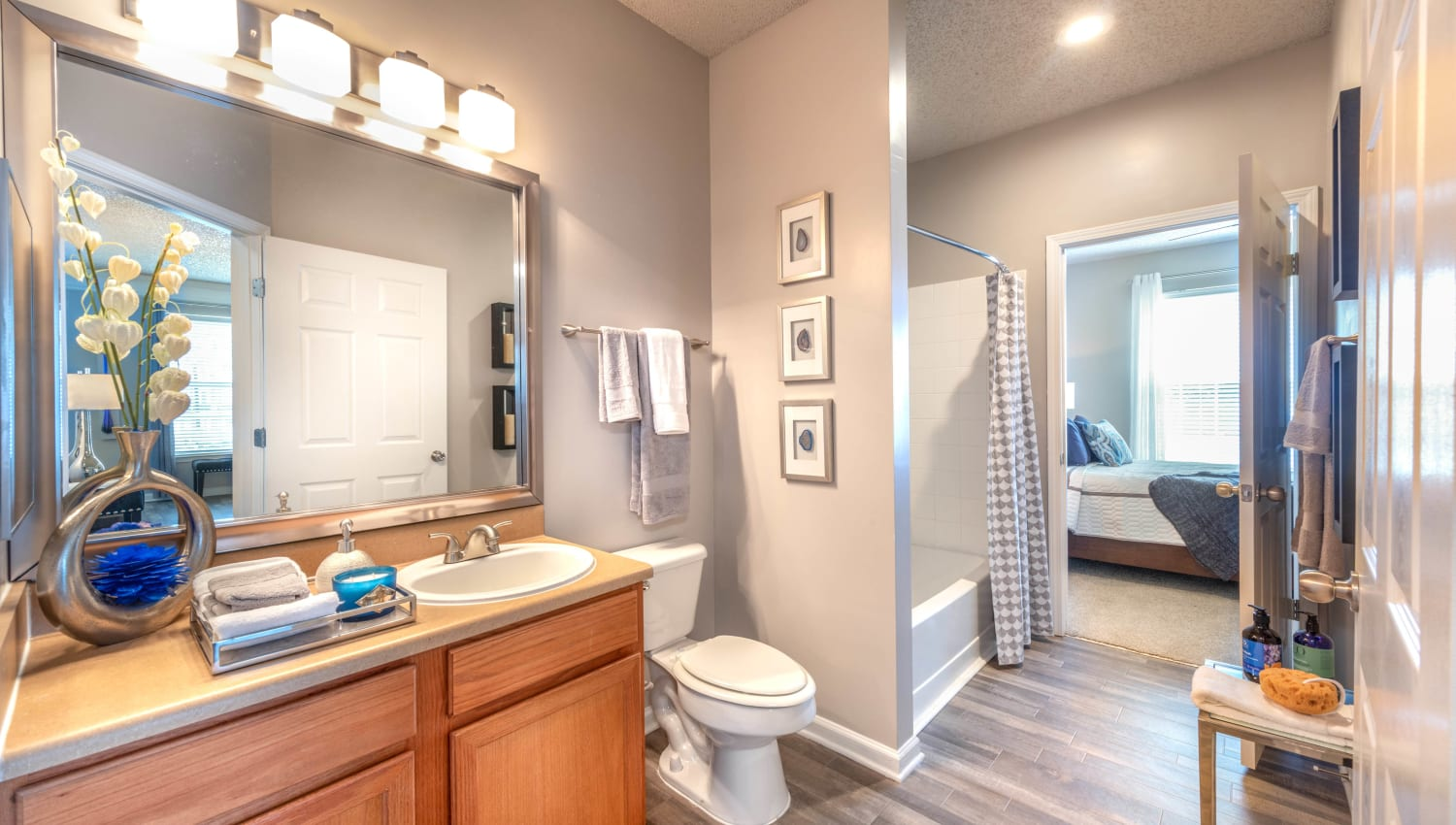 En suite bathroom with hardwood flooring off the master bedroom in a model home at Olympus Fenwick in Savannah, Georgia